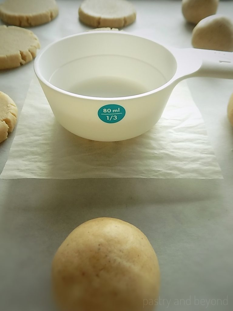 Steps of making Easy Cinnamon Cookies: Flattening the balls with a measuring cup