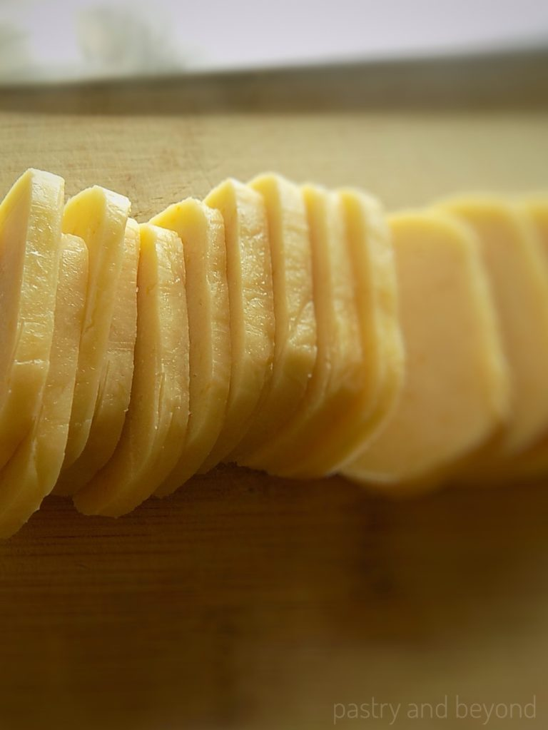 Steps of making lemon slice-and bake cookies: Slicing the cookie dough 1/5 inches (5 millimeters) thick.