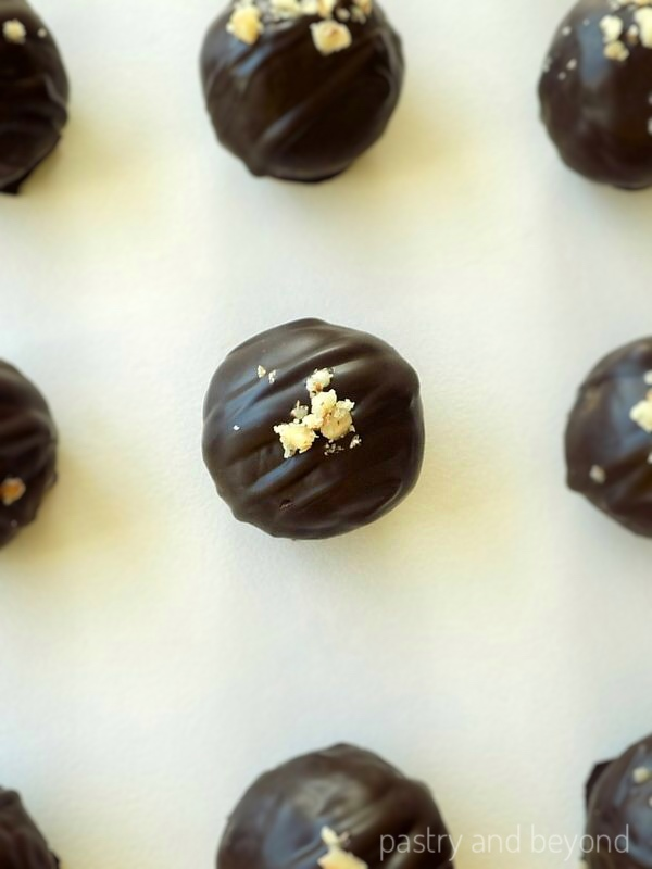 Chocolate covered Healthy Energy Balls on a white surface.