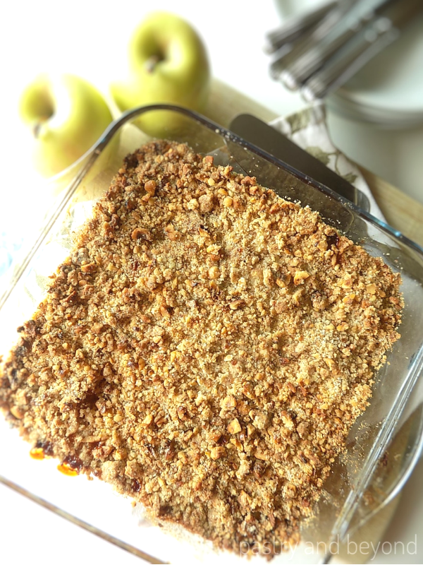 Easy Apple Crumble on a baking dish, golden apples, plates, forks are behind.