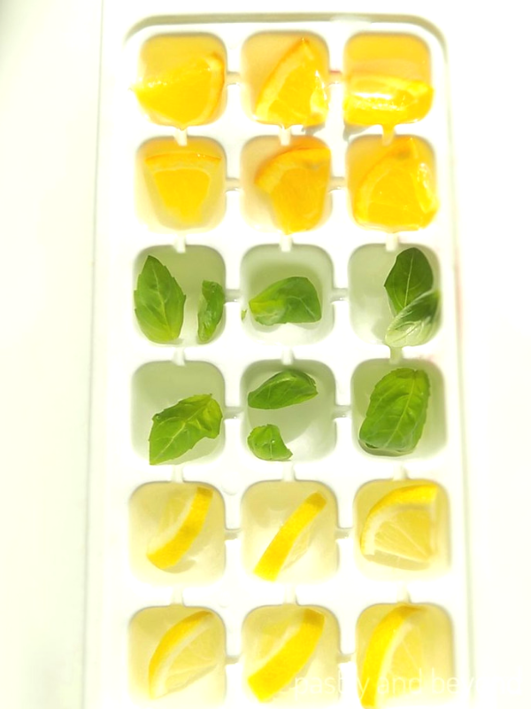 Ice tray filled with lemon, orange, basil leaves and water.