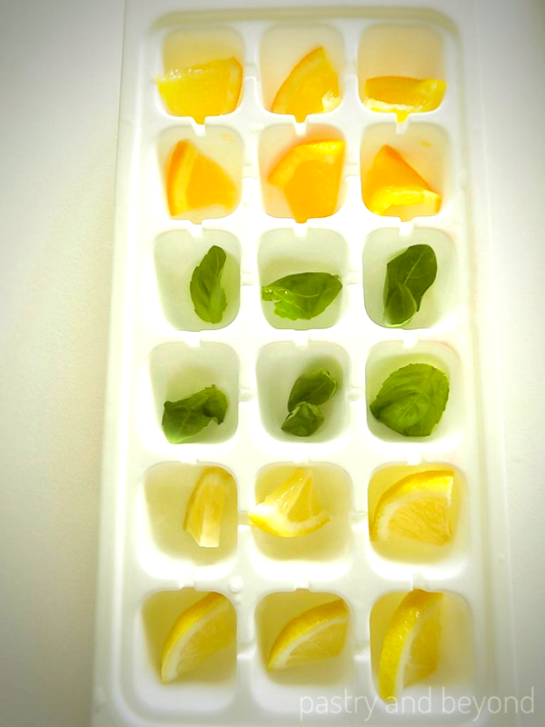 Placing lemon, orange , basil leaves into the ice tray.