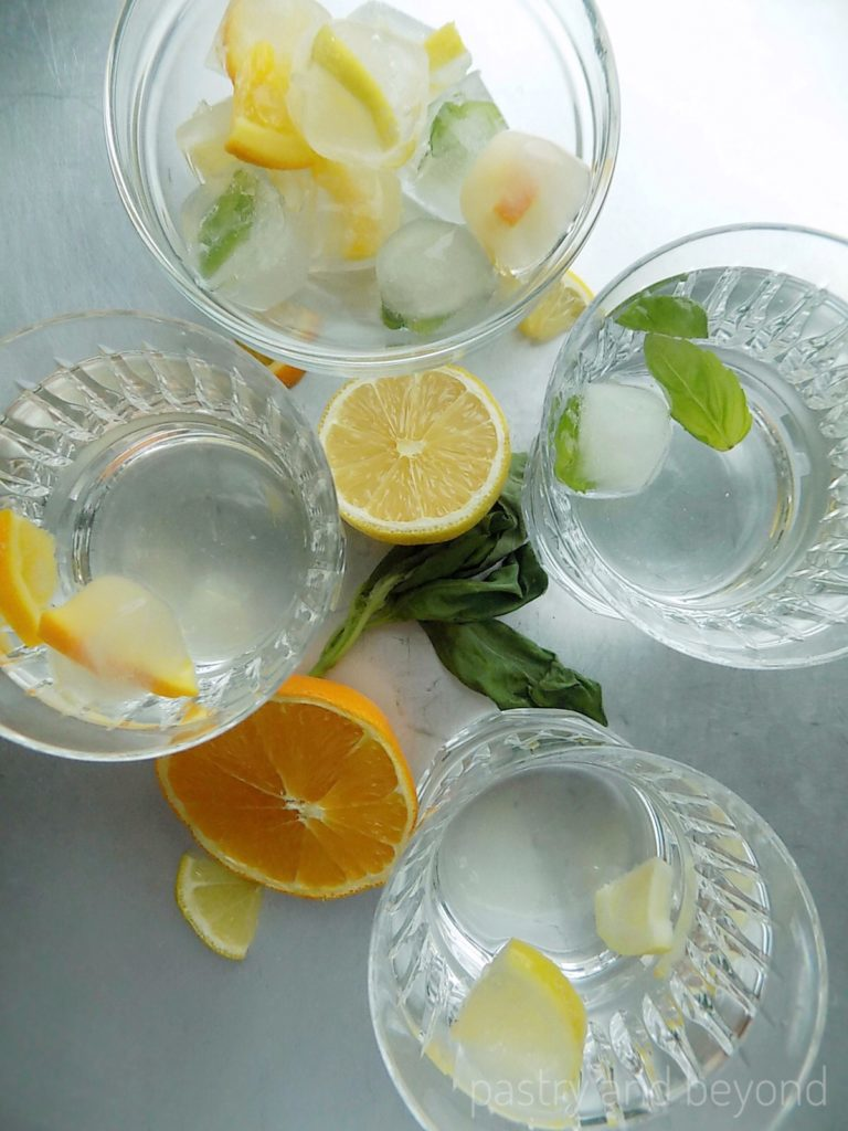 Fancy ice cubes with lemon, orange and basil leaves in glasses