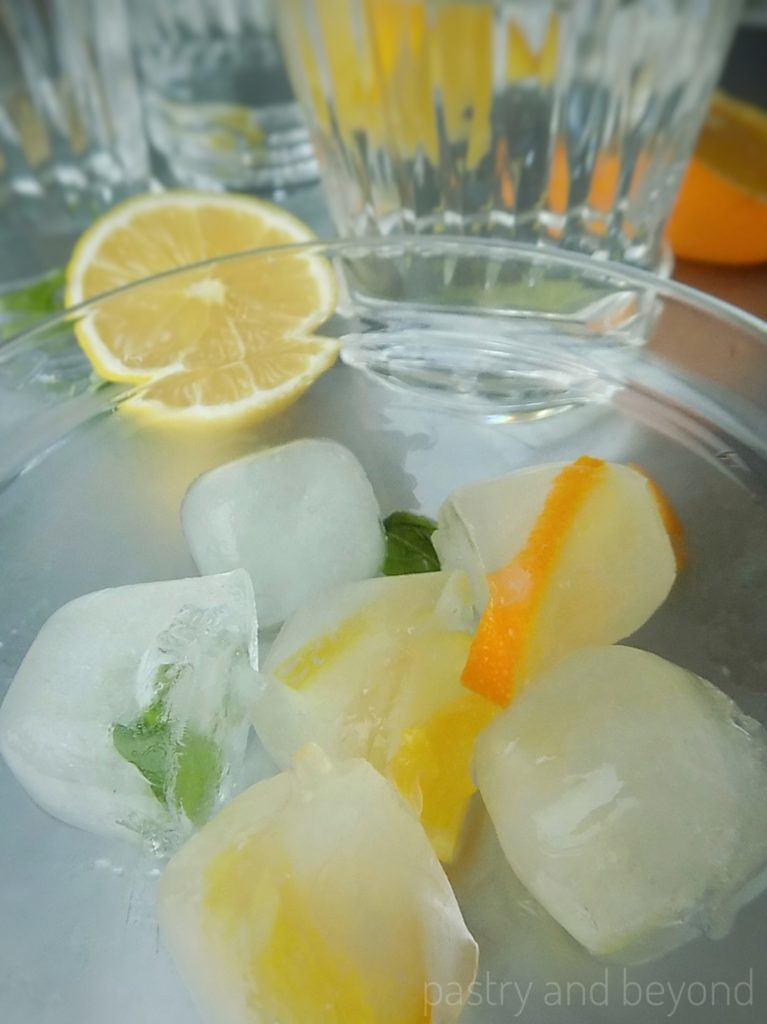 Fancy Ice Cubes with lemon, orange and basil leaves.