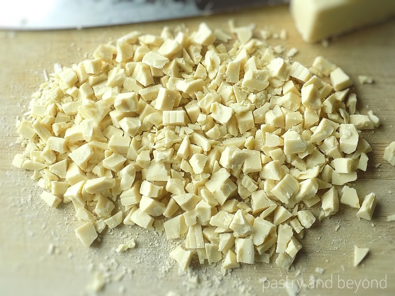White Chocolate roughly cut into small pieces on a chopping board to make double chocolate cookies.