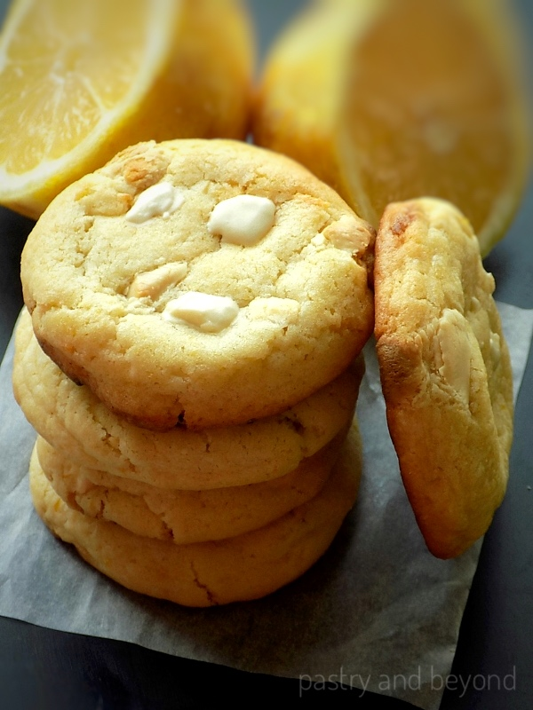 Stacked lemon white chocolate lemon cookies, in front of the lemon that is cut in half