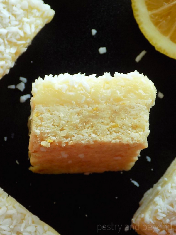 Lemon Coconut bars with white chocolate on a black surface.