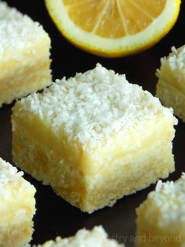 Lemon Coconut Bars and a lemon on a black surface.