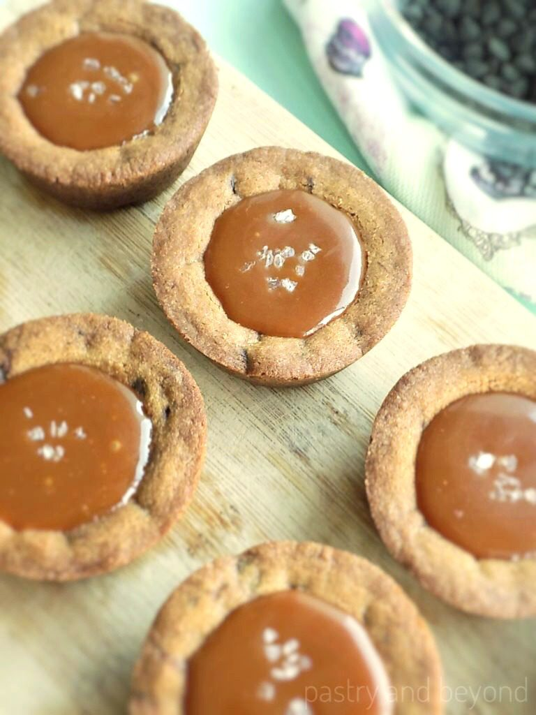 Salted Caramel Chocolate Chip Cookie Cups on a wooden surface.