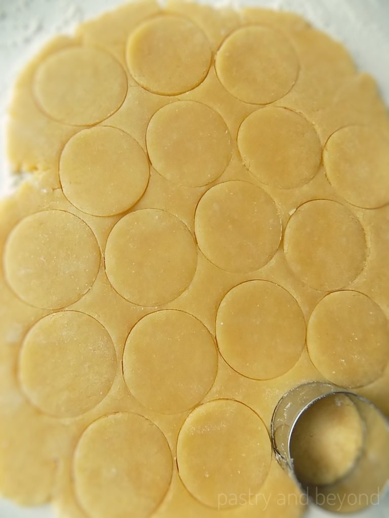 Steps of Making Crunchy Savory Cookies: Rolling out the dough and cutting with a circle cookie cutter.