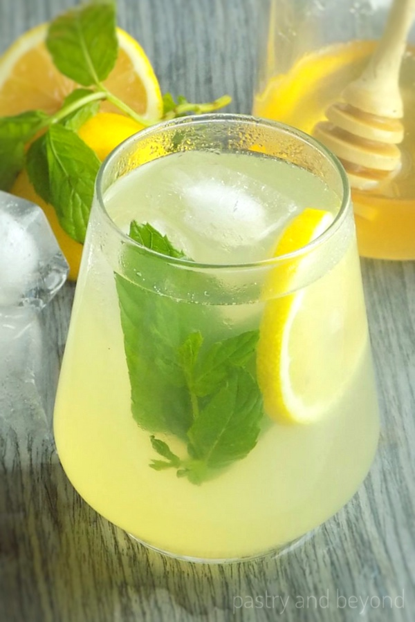 Honey lemonade in a glass with lemon slice and mint.