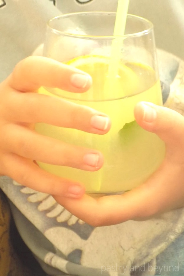 Holding a lemonade glass.