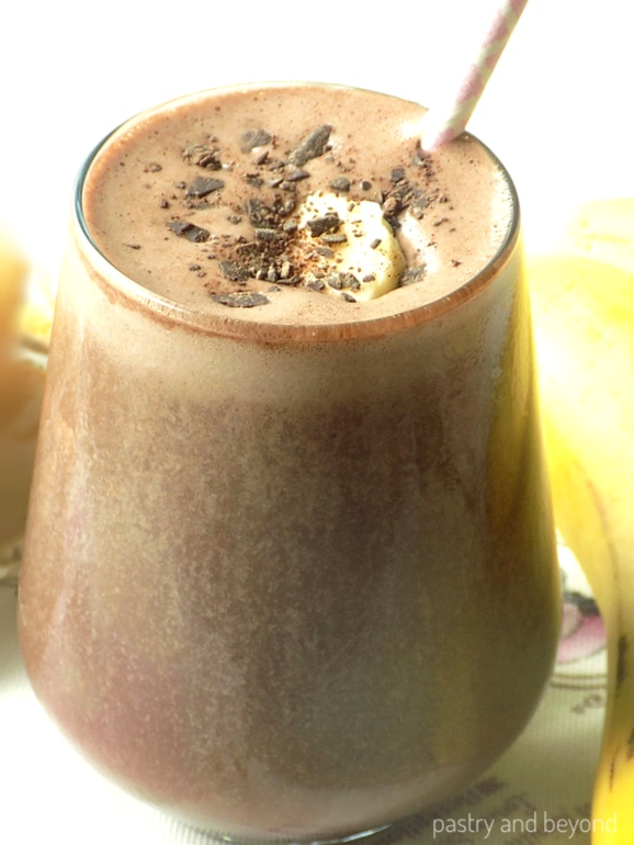 Chocolate Peanut Butter Banana Smoothie in a large glass next to the banana.