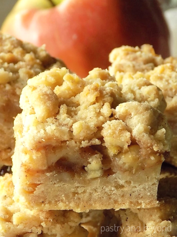 Apple Pie Bars stacked, red apple behind the bars.